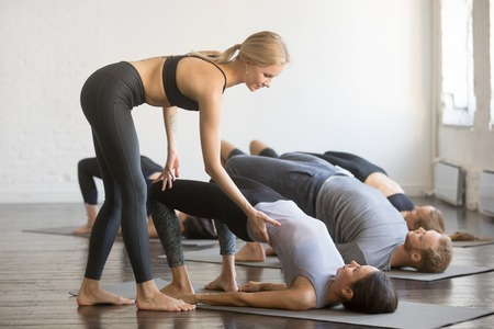 Foto per Group of young sporty people practicing yoga lesson with instructor, stretching, doing Glute Bridge exercise, female teacher correcting dvi pada pithasana pose, working out, indoor full length, studio - Immagine Royalty Free