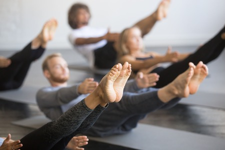 Foto de Group of young sporty people practicing yoga lesson with instructor, stretching in Paripurna Navasana exercise, balance pose, working out, indoor close up image, studio, focus on feet - Imagen libre de derechos