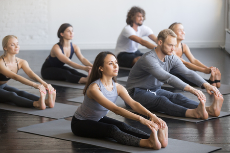 Foto de Group of young sporty people practicing yoga lesson with instructor, sitting in paschimottanasana exercise, Seated forward bend pose, indoor full length, studio, friends working out in club - Imagen libre de derechos
