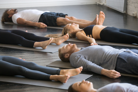 Photo pour Group of young sporty people practicing yoga lesson with instructor in gym, lying in Dead Body exercise, doing Savasana, Corpse pose, friends relaxing after working out in sport club, indoor image - image libre de droit