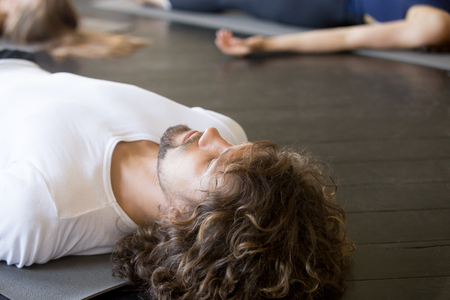 Foto de Close up of male head, young handsome man with curly hair, practicing yoga lesson with group in gym, lying in Dead Body exercise, doing Savasana, Corpse pose, relaxing after working out in sport club - Imagen libre de derechos