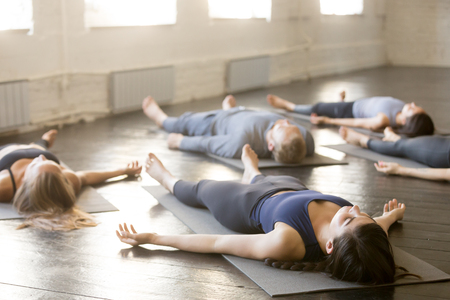 Foto de Group of young sporty people practicing yoga lesson in gym, lying in Corpse exercise doing Savasana pose, friends relaxing after working out in sport club, indoor image. Wellbeing and wellness concept - Imagen libre de derechos