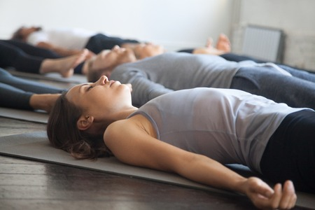 Foto de Group of young sporty people practicing yoga lesson with instructor in gym, lying in Dead Body exercise, doing Savasana, Corpse pose, friends relaxing after working out in sport club, studio image - Imagen libre de derechos
