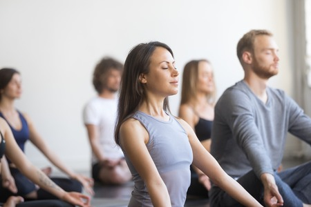 Photo pour Group of young people, sporty students practicing yoga lesson with instructor, sitting and meditating with closed eyes in Padmasana exercise, Lotus pose, friends working out in club, studio background - image libre de droit