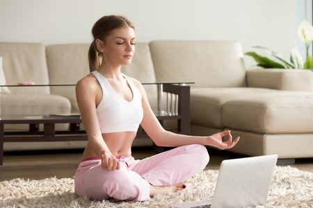 Foto de Young calm woman sits in staff easy lotus pose near laptop at home interior, meditating alone on the floor with eyes closed, online yoga training, doing breathing exercise in the morning, no stress - Imagen libre de derechos