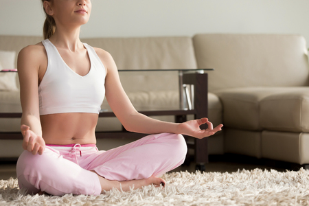Photo pour Calm young woman sitting on the floor in sukhasana easy lotus pose hands in chin mudra gesture, enjoying meditating alone at home interior, practicing yoga for peaceful mind at morning, close up view - image libre de droit
