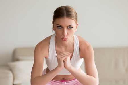 Photo for Young sporty slim woman doing squat morning exercise, practicing breathing correctly during working out home routine, looking at camera, holding hands together exhaling on muscular exertion, portrait - Royalty Free Image
