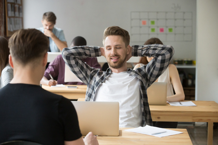 Foto de Smiling young male entrepreneur relaxing stretching back at workplace in shared office. Taking a break from heavy workflow, chilling after positive meeting, finished project, done with work concept. - Imagen libre de derechos