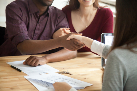 Photo for African american man shaking hands with real estate agent, contract and keys on table. Husband and wife signed rental agreement. Young multiethnic couple purchased new home concept. Close up view - Royalty Free Image
