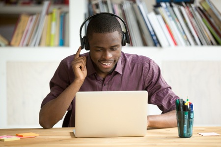 Foto de Smiling african american office worker in headphones looking at laptop screen. Young  casual businessman studying foreign language, communicating with clients through video conference application. - Imagen libre de derechos