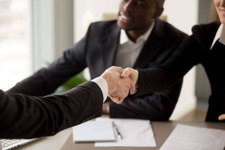 Foto de Close up image of business handshake between caucasian businesswoman and client or partner on multinational meeting in office. Job applicant introducing himself to company HR management on interview - Imagen libre de derechos