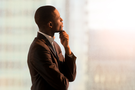 Photo pour Portrait of pensive african american businessman standing near window and thinking about decision, dreaming of success, pondering new startup. Handsome black business leader imagining company future - image libre de droit