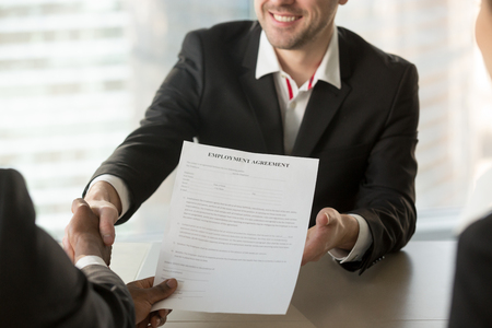 Foto per Boss or human resources manager handshaking with male job candidate, offering employment agreement document. HR manager congratulating new company worker after successful job interview. Close up view - Immagine Royalty Free