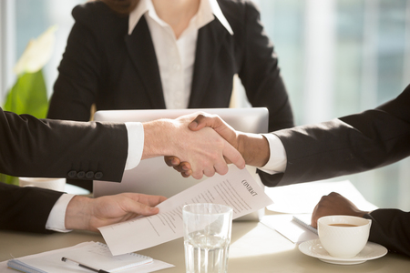 Photo pour Multi-ethnic businesspeople shaking hands at negotiation table after singing contract in presence of female secretary, notary or lawyer. Strong handshake between partners making good deal. Close up - image libre de droit