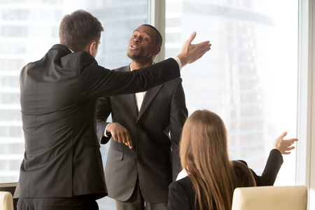 Photo pour Ambitious african american male candidate insisting on getting a job, male and female caucasian recruiters asking quarrelsome applicant to leave office. Failed interview, conflict at work or dismissal - image libre de droit