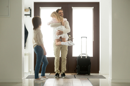 Photo pour Happy father arrived home returning after business trip with baggage, daddy missed little daughter holding in arms hugging girl while wife standing in hall, family reunion, welcome back dad concept - image libre de droit