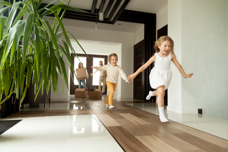 Foto de Happy young family with cardboard boxes in new home at moving day concept, excited children running into big modern own house hallway, parents with belongings at background, mortgage loan, relocation - Imagen libre de derechos