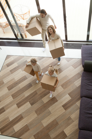 Foto de Young family with kids entering new home carrying boxes, children helping parents to relocate into big modern house with terrace on moving in day concept, mortgage and relocation, vertical top view - Imagen libre de derechos