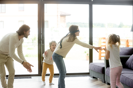 Photo for Blindfolded mother playing hide and seek game with father and kids hiding clapping hands at home, happy family having fun together on leisure in living room, parents children activities on weekend - Royalty Free Image