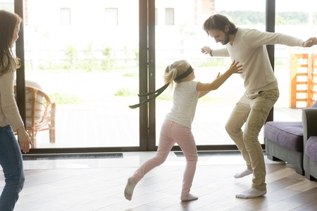 Photo for Little girl catching father playing hide and seek, preschool blindfolded daughter having fun with mom and dad at home, parents with kid spending time together in living room on leisure, family games - Royalty Free Image