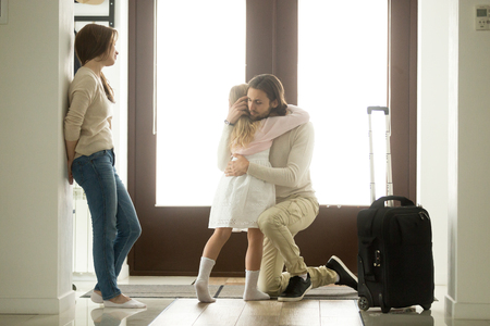 Foto de Sad father hugging little daughter before leaving for long business trip, upset dad embracing crying girl saying goodbye to daddy at home in hall with baggage, family separation, good bye, farewell - Imagen libre de derechos