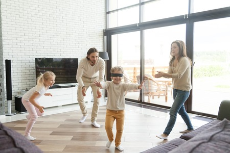 Photo for Blindfolded little boy playing hide and seek game at home, happy family of four having fun enjoying leisure activity in living room, parents and kids laughing spending free time together on weekend - Royalty Free Image