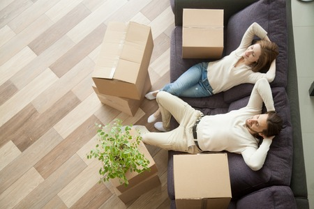 Foto de Couple resting on couch after moving in, man and woman relaxing on sofa just moved into apartment with cardboard boxes on floor, happy satisfied homeowners enjoying first day in new home, top view - Imagen libre de derechos