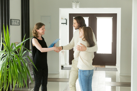 Photo for Friendly  and young couple shaking hands standing in hallway, real estate agent handshaking clients at meeting, showing selling buying property for rent sale, discussing deal with customers - Royalty Free Image