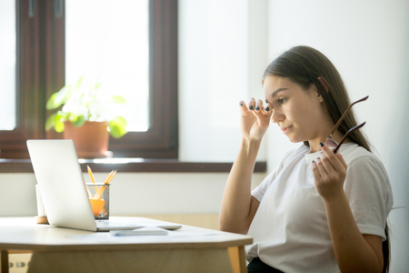Photo for Young female worker with tired eyes holding glasses. Woman feeling discomfort from long wearing eyeglasses behind laptop at workplace. Eyesight strain from computer work concept - Royalty Free Image
