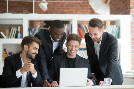 Photo for Multi-ethnic smiling businessmen in suits watching something funny on laptop in office together, diverse excited business team happy to see good news or work result profit growth on computer screen - Royalty Free Image