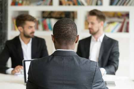 Photo pour Rear view at african businessman against two caucasian men wearing suits, black vacancy candidate sitting his back to camera on job interview with two employers, hr, colleagues or recruiters concept - image libre de droit