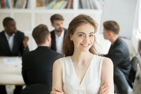 Photo for Attractive female leader standing with arms crossed in front of male executive team meeting, smiling businesswoman looking at camera, friendly woman boss, assistant or hr manager headshot portrait - Royalty Free Image