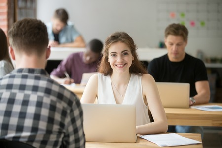 Foto de Portrait of smiling attractive woman looking at camera sitting at desk in co-working, young freelancer student intern employee working in shared office, businesswoman with laptop in coworking space - Imagen libre de derechos
