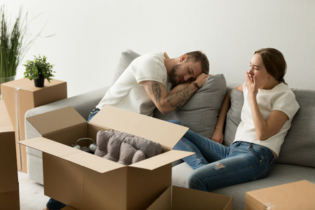 Photo pour Young tired couple feeling fatigue on long hard moving out day, exhausted restless man having break in new home while sleepy woman yawning on sofa after packing staff in boxes preparing to relocate - image libre de droit