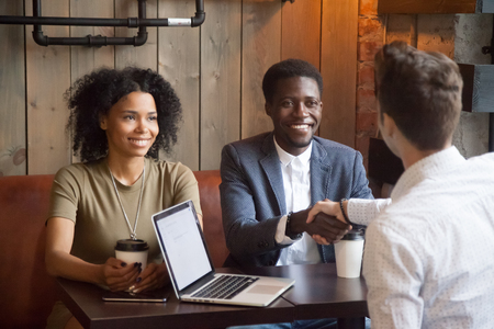 Photo for Smiling african american couple shaking hands to mortgage insurance broker, financial advisor or agent at cafe meeting, happy black woman and man handshaking white lawyer or consultant making deal - Royalty Free Image