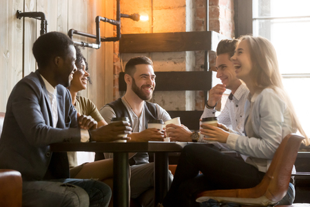 Foto de Multiracial friends having fun and laughing drinking coffee in coffeehouse, diverse young people talking joking sitting together at cafe table, multi ethnic millennials spending time in coffee shop - Imagen libre de derechos