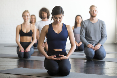 Foto de Group of young sporty people practicing yoga lesson with instructor, sitting in vajrasana pose, working out, indoor full length, students training in club, studio. - Imagen libre de derechos