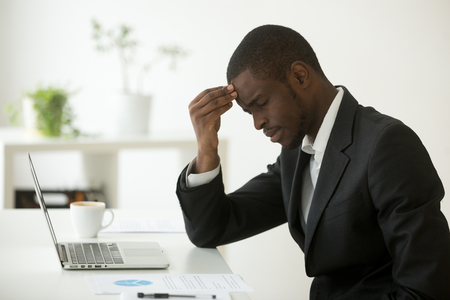 Foto de Headache at work concept, stressed african-american businessman feels strong sudden migraine working on laptop at workplace, frustrated dizzy black man in suit touching head tired of chronic fatigue - Imagen libre de derechos