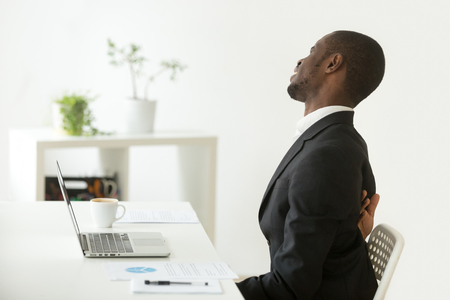 Foto de African businessman feels strong backache sitting on uncomfortable office chair at work, black man in suit suffering from ache pain in tensed back muscles after sedentary work in incorrect posture - Imagen libre de derechos