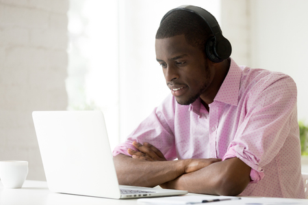 Foto de African american man wearing headphones using laptop looking at computer screen, smiling young black businessman learning studying online, watching video or making call with pc internet application - Imagen libre de derechos