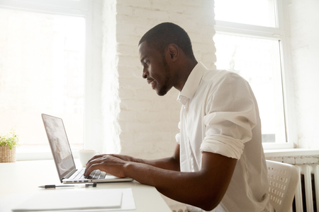 Photo for African businessman working on laptop sitting at home office desk, happy black intern employee looking at computer screen typing or browsing web, using software application for business and education - Royalty Free Image