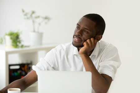 Photo pour Dreamy african american young man thinking of new idea at workplace, black lazy worker avoiding work lost in thoughts, absent-minded intern dreaming of successful business and happy future career - image libre de droit