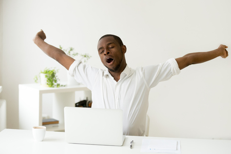 Foto de Sleepy african american man stretching yawning at workplace, tired black lazy worker feels lack of sleep fatigue taking rest for relaxing morning coffee break sitting at home office desk with laptop - Imagen libre de derechos