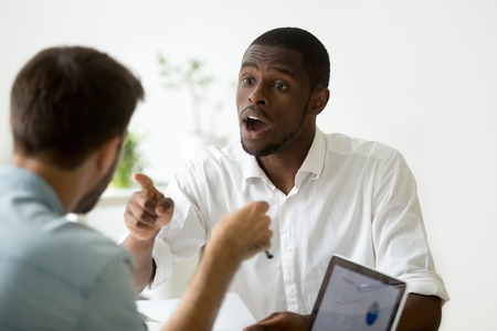 Foto de African american businessman disagreeing arguing debating during office negotiations, black negotiator disputing with caucasian partner, insisting on point of view in discussion, explaining opinion - Imagen libre de derechos
