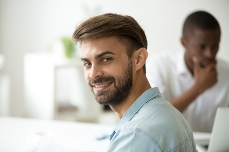 Photo for Smiling young caucasian entrepreneur, ambitious intern or successful professional looking at camera working with african colleague in office, happy white job applicant at interview, headshot portrait - Royalty Free Image