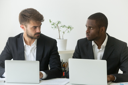 Foto de Multiracial office rivals looking at each other with hate envy sitting with laptops, corporate competitors african and caucasian employees compete in business work, team rivalry at workplace concept - Imagen libre de derechos
