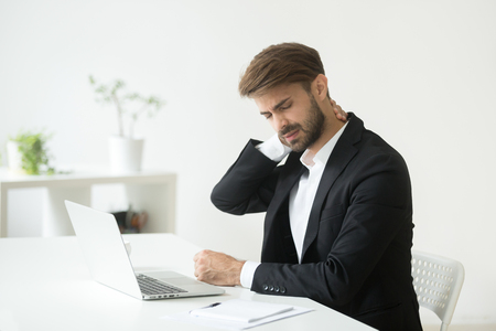 Photo for Young businessman in suit feels neck pain massaging tensed muscles after sedentary work sitting on uncomfortable office chair, employee having computer syndrome suffers from chronic cervicalgia ache - Royalty Free Image