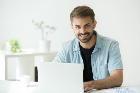 Photo for Smiling businessman working with statistics and laptop in office, friendly entrepreneur freelancer looking at camera at workplace, happy intern or marketing seo manager using computer, portrait - Royalty Free Image
