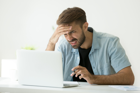 Photo for Confused young man frustrated by online problem looking at laptop screen, worker troubled doing hard job on computer making notes, student feels stressed about difficult learning failing test or exam - Royalty Free Image