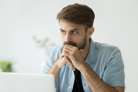 Photo for Thoughtful serious young man lost in thoughts in front of laptop, focused businessman or absent-minded student thinking of problem solution, worried puzzled manager pondering question at work - Royalty Free Image